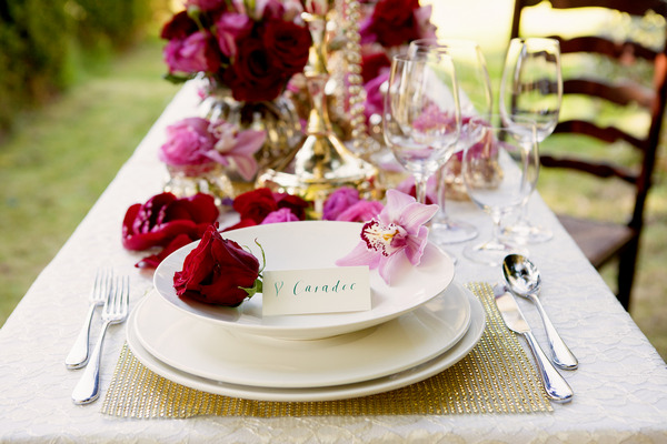 Plate and charger with rose on styled wedding table