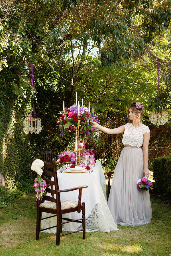 Bride standing next to long styled wedding table