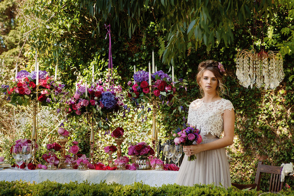 Bride holding bouquet standing next to long styled wedding table