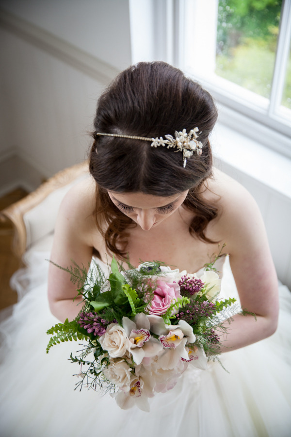 Bride looking down at bouquet to show headband