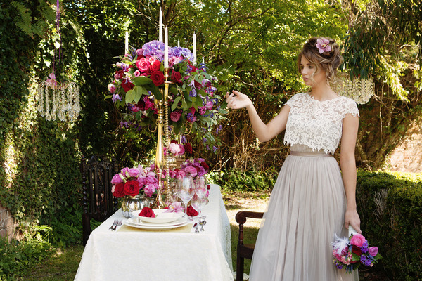 Bride next to styled wedding table in garden at Tros Yr Afon