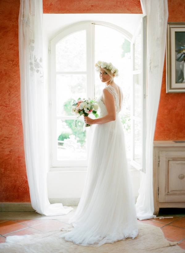 Bride with flower crown holding bouquet by window