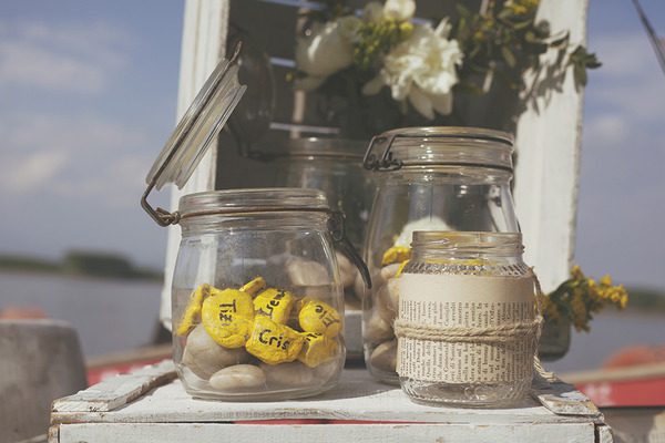 Jar of yellow painted pebbles for wedding place names