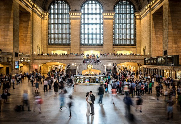 Bride and groom in train station with passengers moving around them - Picture by James Tracey Photography