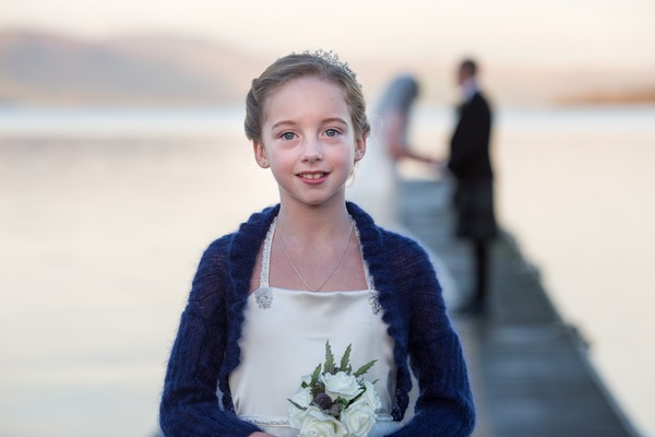 Flower girl standing on jetty with bride and groom in background - Picture by Lorraine Bhandari Photography and Videography