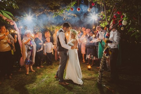 Bride and groom under tree surrounded by wedding guests - Picture by Nick Ray Photography