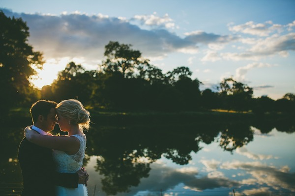 Bride and groom standing by lake at sunset - Picture by Rob Dodsworth Photography