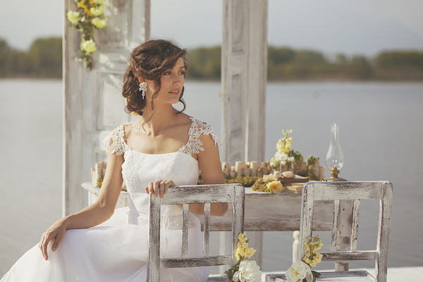 Bride sitting on rustic chair by lake