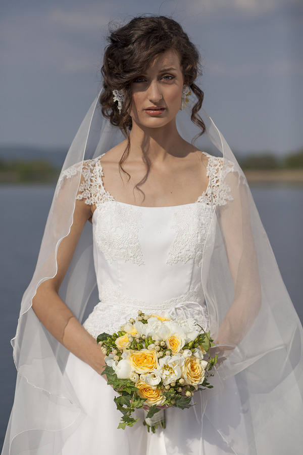 Bride holding spring wedding bouquet of yellow flowers