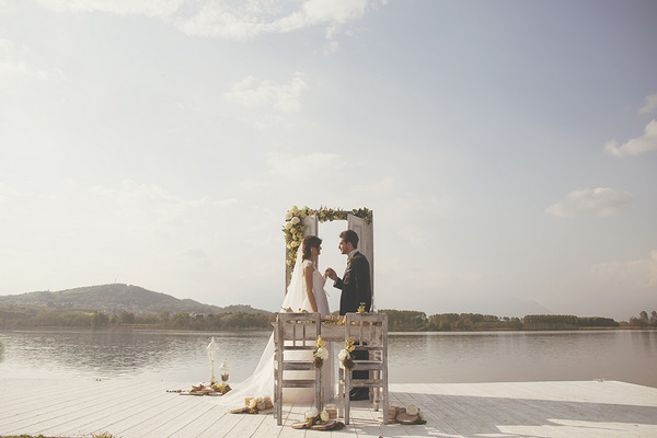 Bride and groom on jetty by Lake of Candia in Italy