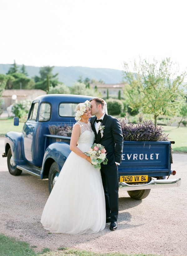 Bride and groom kissing in front of Chevrolet filled with lavender