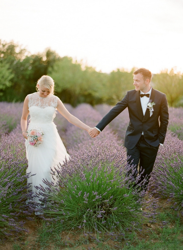 Bride and groom holding hands in field of lavender in Provence