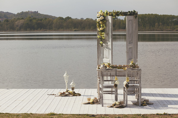 Table with spring flowers on jetty by lake in Italy