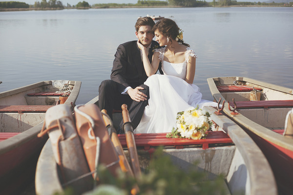 Bride and groom sitting on rowing boat on lake in Italy
