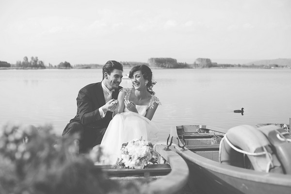 Bride and groom laughing on rowing boat on lake in Italy