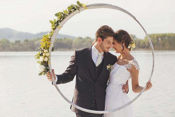 Bride and groom holding up hoop