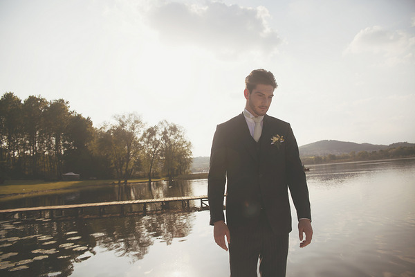 Groom standing by Lake of Candia in Italy