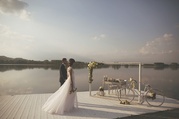 Bride and groom walking across jetty to wedding table