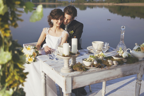 Bride and groom sitting at wedding table by Lake of Candia in Italy