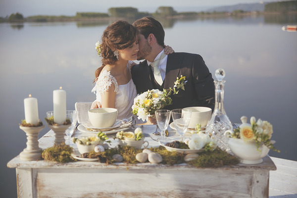 Bride and groom sitting at wedding table by lake
