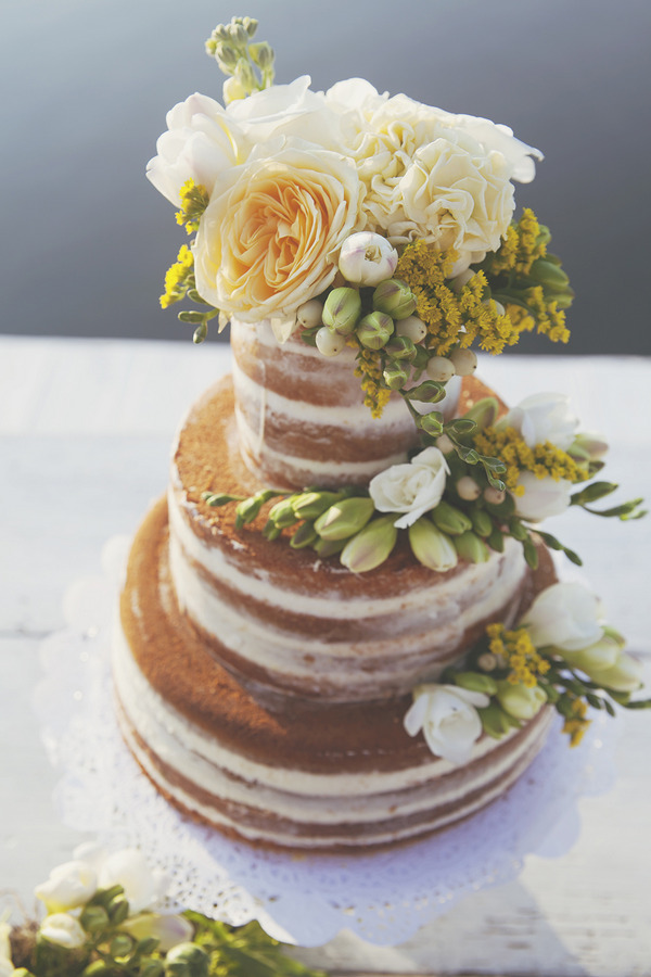 Naked wedding cake with yellow flowers
