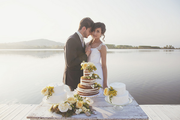 Bride and groom standing by wedding cake table