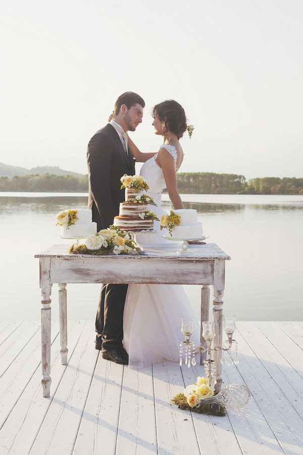 Bride and groom by wedding cake table in front of Lake of Candia in Italy