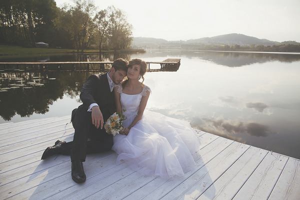 Bride and groom sitting on jetty by Lake of Candia in Italy