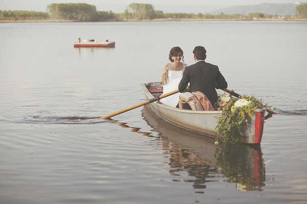 Bride and groom in rowing boat on lake in Italy