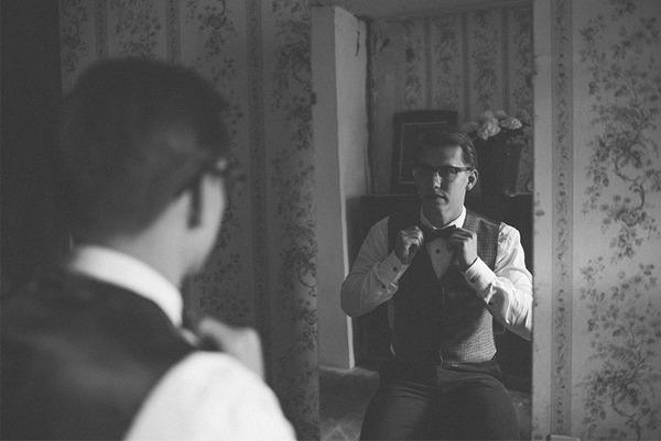 Groom adjusting bow tie in mirror
