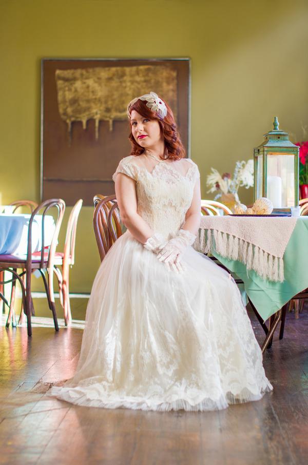 Bride wearing vintage wedding dress sitting on chair