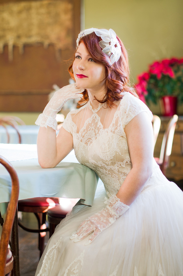 Bride wearing vintage wedding dress and gloves, leaning on table
