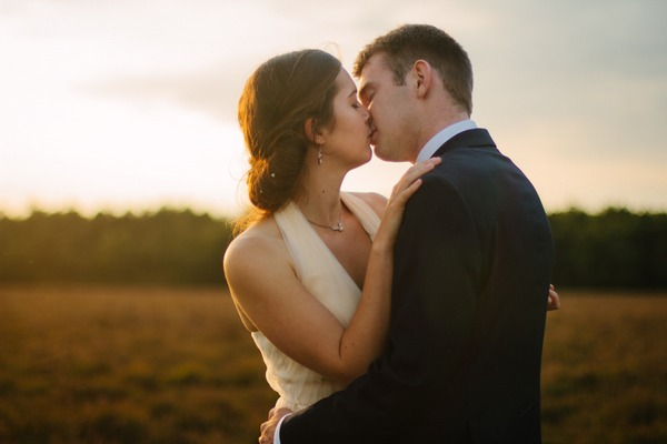 Bride and groom kissing in a field - Picture by Nisha Haq Photography