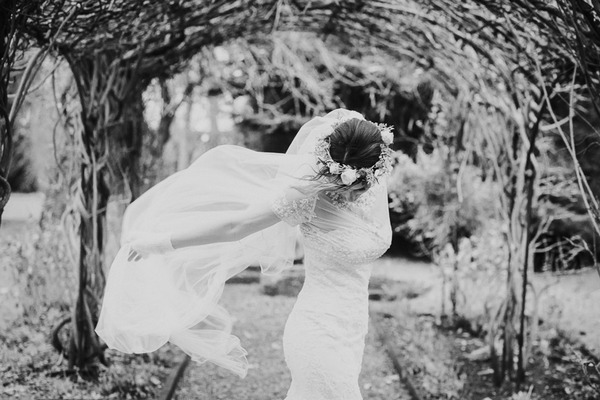 Bride with flower crown and flowing veil looking down - Picture by Samantha Jane Photography
