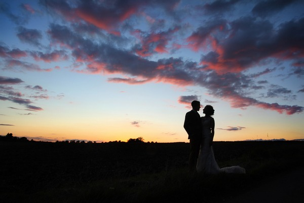 Silhouette of bride and groom against colourful night sky - Picture by David Michael Photography