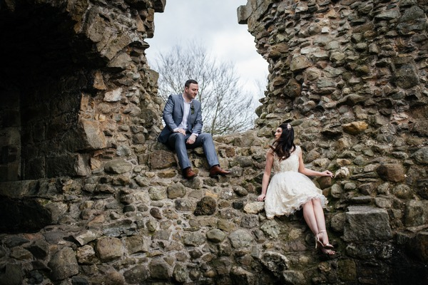 Bride and groom sitting on wall - Picture by Jess Yarwood Photography