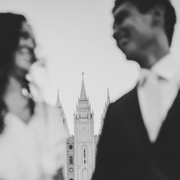 Bride and groom with building in background between them - Picture by India Earl Photography