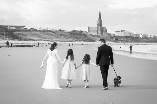 Bride, groom and young bridesmaids walking across a beach with their dog - Picture by Matt Hale Photography