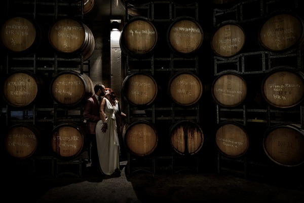 Bride and groom kissing in front of racks of barrels - Picture by D'Amico Photography