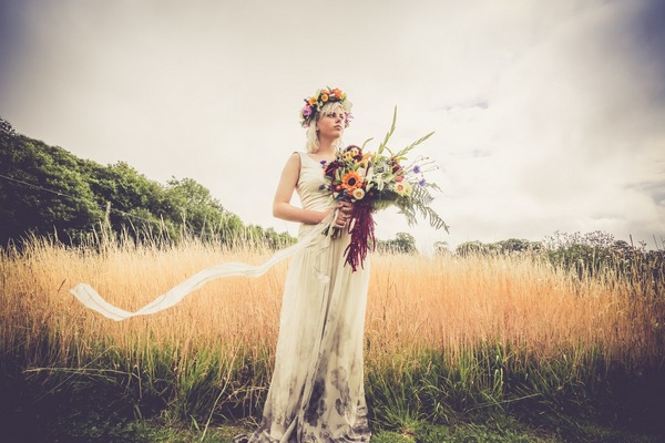 Bride with flower crown and large bouquet standing by field of wheat - Picture by Velvet Storm Photography