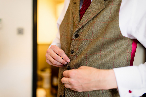 Groomsman doing up tweed waistcoat