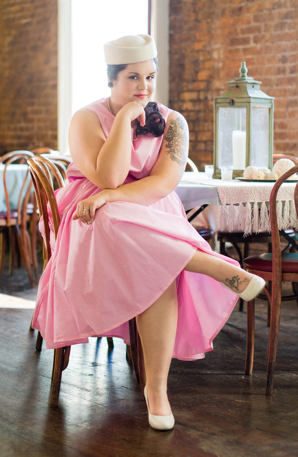 Bride in retro pink wedding dress sitting on chair