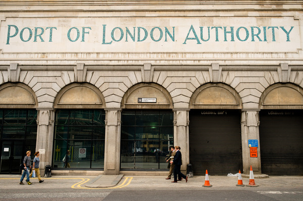 Groomsmen walking past Post of London Authority sign