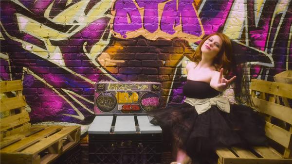 Bride in black wedding dress sitting next to graffiti wall