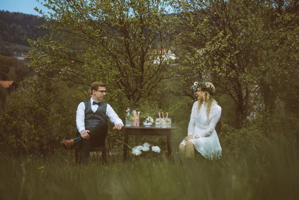 Bride and groom sitting at table in Slovenian countryside