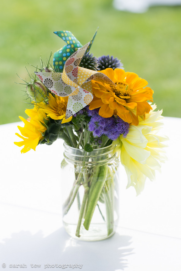 Jar of bright wedding flowers with pinwheel