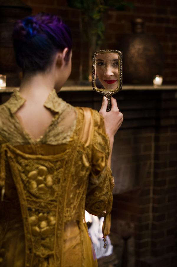 Bride in gold vintage wedding dress looking in mirror