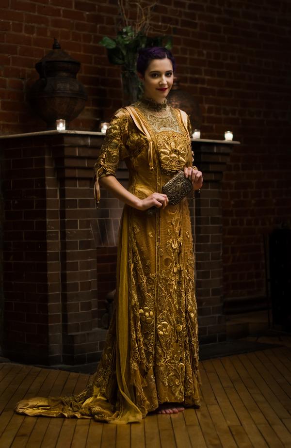 Bride in gold vintage wedding dress holding mirror