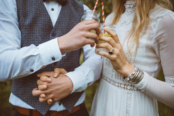 Bride and groom holding jam jars of lemonade