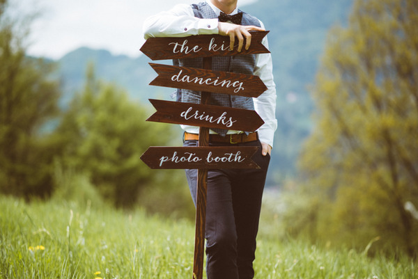Groom leaning on wedding sign